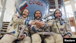 Russian cosmonauts Pavel Vinogradov (center) and Aleksandr Misurkin (left) pose with U.S. astronaut Christopher Cassidy for a photograph before taking an exam at the cosmonaut training center in Star City, outside Moscow, in early March.