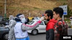 Health workers screening travelers on the road from the capital Tehran to Chaloos in the north of Iran. March 26, 2020.