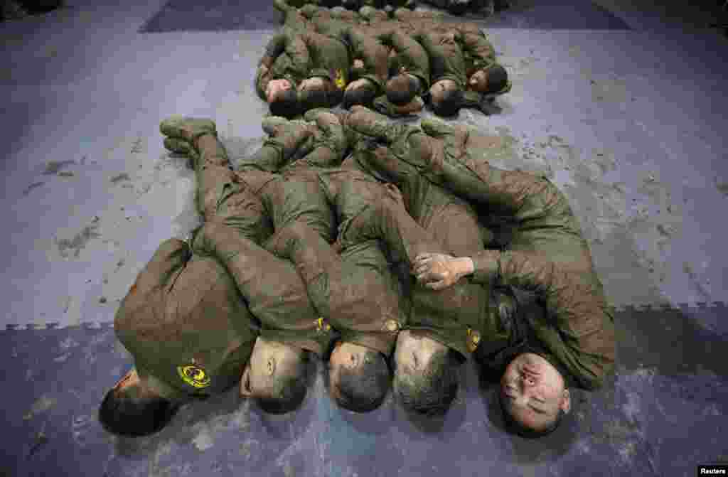 Cadets hold each other for warmth as they sleep during a break from high intensity training at the Tianjiao Special Guard/Security Consultant camp on the outskirts of Beijing, China. (Reuters/Jason Lee)