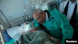 """Иемен денсаулық сақтау министрі Ахмад әл-Анси """"Әл-Қаида"""" шабуылынан жараланған офицердің жанында отыр. Сана, 6 желтоқсан 2013 жыл."""
