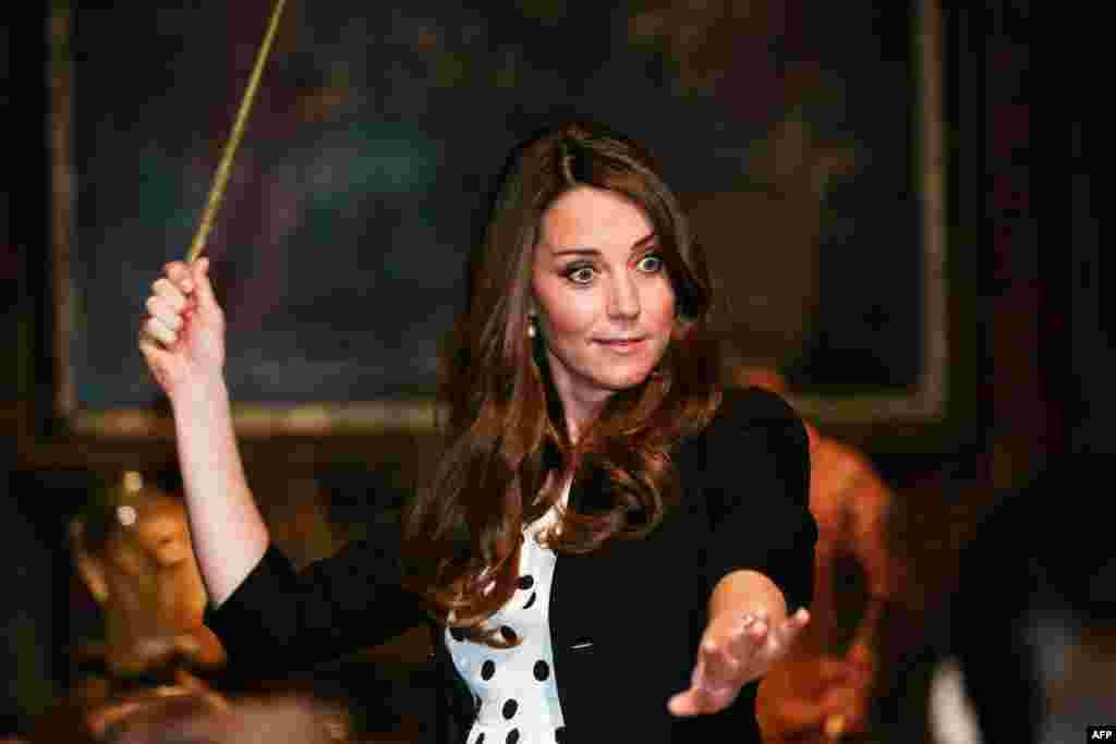 Britain's Catherine, duchess of Cambridge, tries a wand in the Harry Potter Tour during a visit to the inauguration of the Warner Bros. Studios Leavesden in north London. (AFP/Paul Rogers)