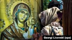 Македонська православна віруюча запалює свічку перед зображенням Богородиці біля церкви в Скоп'є. Серпень 2017 року