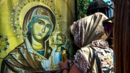A Macedonian Orthodox believer lights candles outside the St. Mother of God church in Skopje, Macedonia, in August 2017.