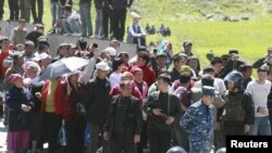 Riot police form a line near people who gathered at the settlement of Nizhnaya Alaarcha outside Bishkek on April 20.