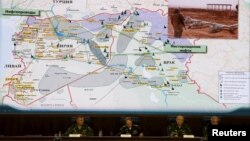 Russian Defense Ministry officials sit under a display showing the Turkish-Syrian border during a briefing in Moscow on December 2 regarding its accusations of Ankara's involvement in the illegal IS oil trade.