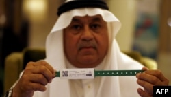 A Saudi official displays an electronic identification bracelet that Saudi authorities are giving to pilgrims ahead of the hajj.