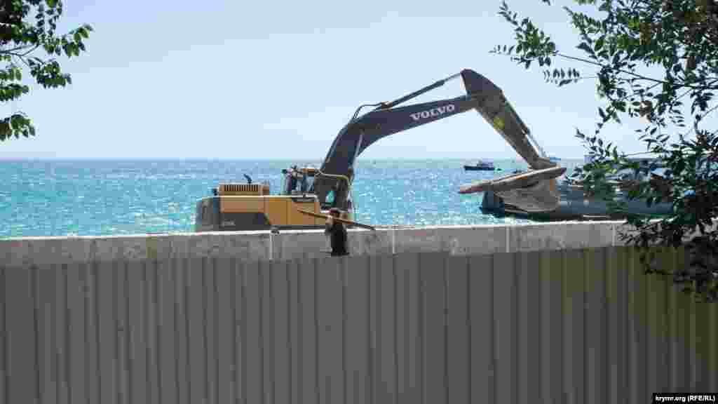 За забором работает строительная техника– экскаватор снимает с набережной железобетонные плиты
