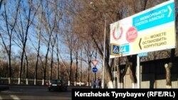 Жемқорлықпен күресуге шақырған жарнама жанында тұрған ішкі істер әскери қызметкерлері. Алматы, 21 наурыз 2015 жыл.
