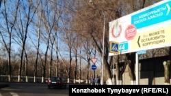 Жемқорлықты жоюға үндейтін жарнама жанында тұрған ішкі істер әскери қызметкерлері. Алматы, 21 наурыз 2015 жыл. Көрнекі сурет.