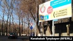 Полицейские рядом с билбордом, призывающим к борьбе с коррупцией. Алматы, 21 марта 2015 года.