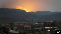 Explosions are seen over the mountains from Stepanakert, the main city of the breakaway Nagorno-Karabakh region, on October 30.