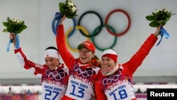 Belarusians gold medalist Darya Domracheva (center) and bronze medalist Nadezhda Skardino (right) celebrate during the flower ceremony for the women's biathlon 15-kilometer individual event at the 2014 Sochi Winter Olympics on February 14.