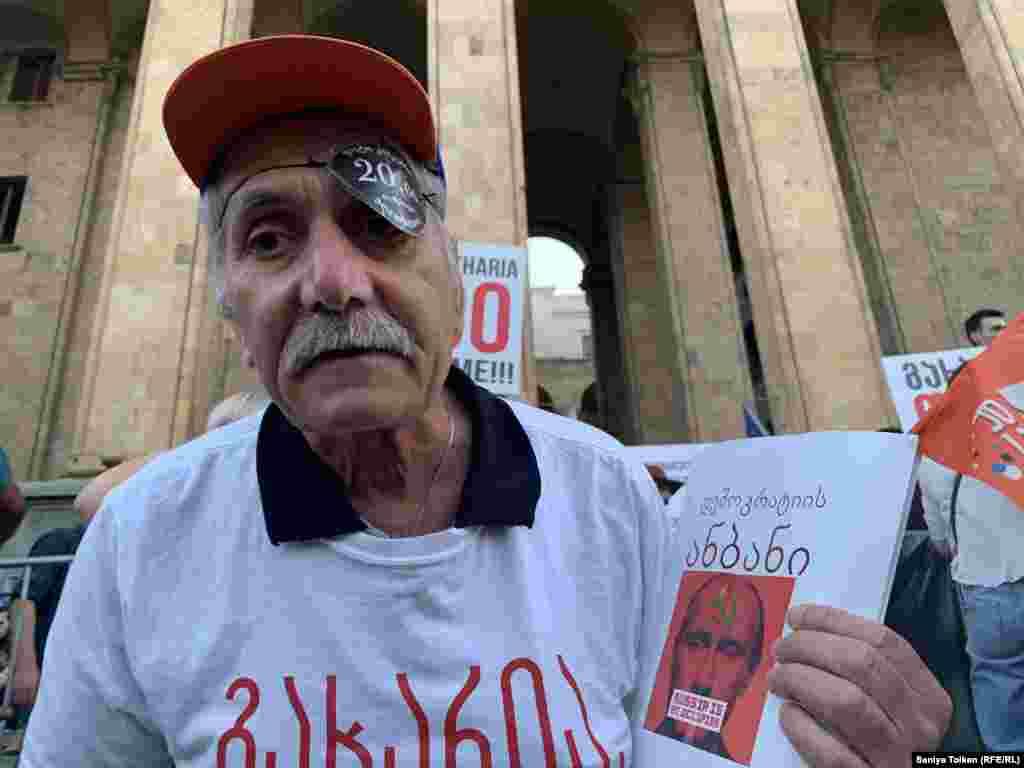 """Қолына грузин тілінде """"Демократия әліппесі. Ресей - басқыншы"""" деген жазу бар кітапша ұстап тұрған наразы азамат. Тбилиси, 3 шілде 2019 жыл."""