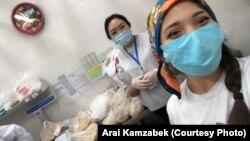 Волонтер Арай Камзабек с другим волонтером расфасовывают продукты. 12 апреля 2020 года.