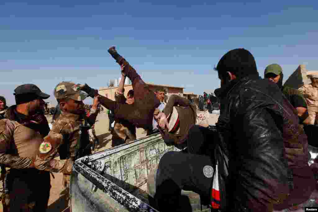 "Iraqi soldiers dump a suspected Islamic State fighter into a pickup truck on February 26. An Iraqi Army commander told Reuters that, unlike Iraqi-born militants fighting with Islamic State, foreign jihadis have no chance of escaping the city undetected and ""will therefore fight to the end."""