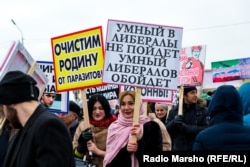 "Rally participants hold placards saying ""We will rid the motherland of parasites"" and ""A smart person doesn't become a liberal. A smart person avoids liberals."""
