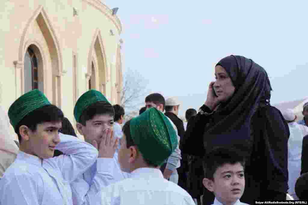 Хлопці в святковому національному вбранні, жінка традиційно в хіджабі