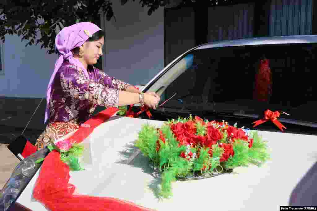 Groom's relatives are getting ready to go for the bride. In this photo, a woman decorates a car on which Roza will be taken to the house of her future husband.