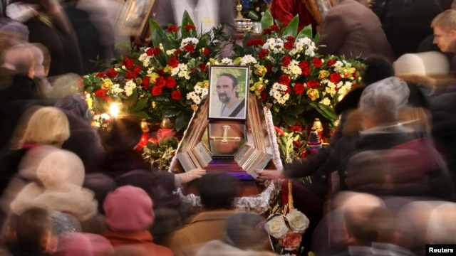 People walk around the coffin of Yuriy Verbytskyy, an antigovernment activist, at his funeral in Lviv on January 24.
