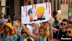 Зображення поцілунку президента США Дональда Трампа та президента Росії Володимира Путіна на плакаті активістів під час протесту у Гельсінкі, 15 липня 2018 року