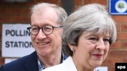 British Primer Minister Theresa May and her husband Philip arrive at a polling station near Reading, England, to cast their votes in the United Kingdom's general election on June 8.