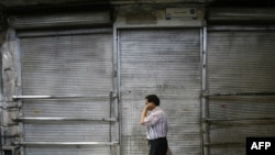 A man walks past a shuttered shop in Tehran's Bazaar.