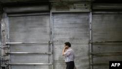 A man walks past a shuttered shop in Tehran's Bazaar.