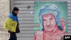 Наразылық шеруіне қатысушы Янукович пен Путин бейнеленген карикатураның қасынан өтіп барады. Киев, 12 желтоқсан 2013 жыл