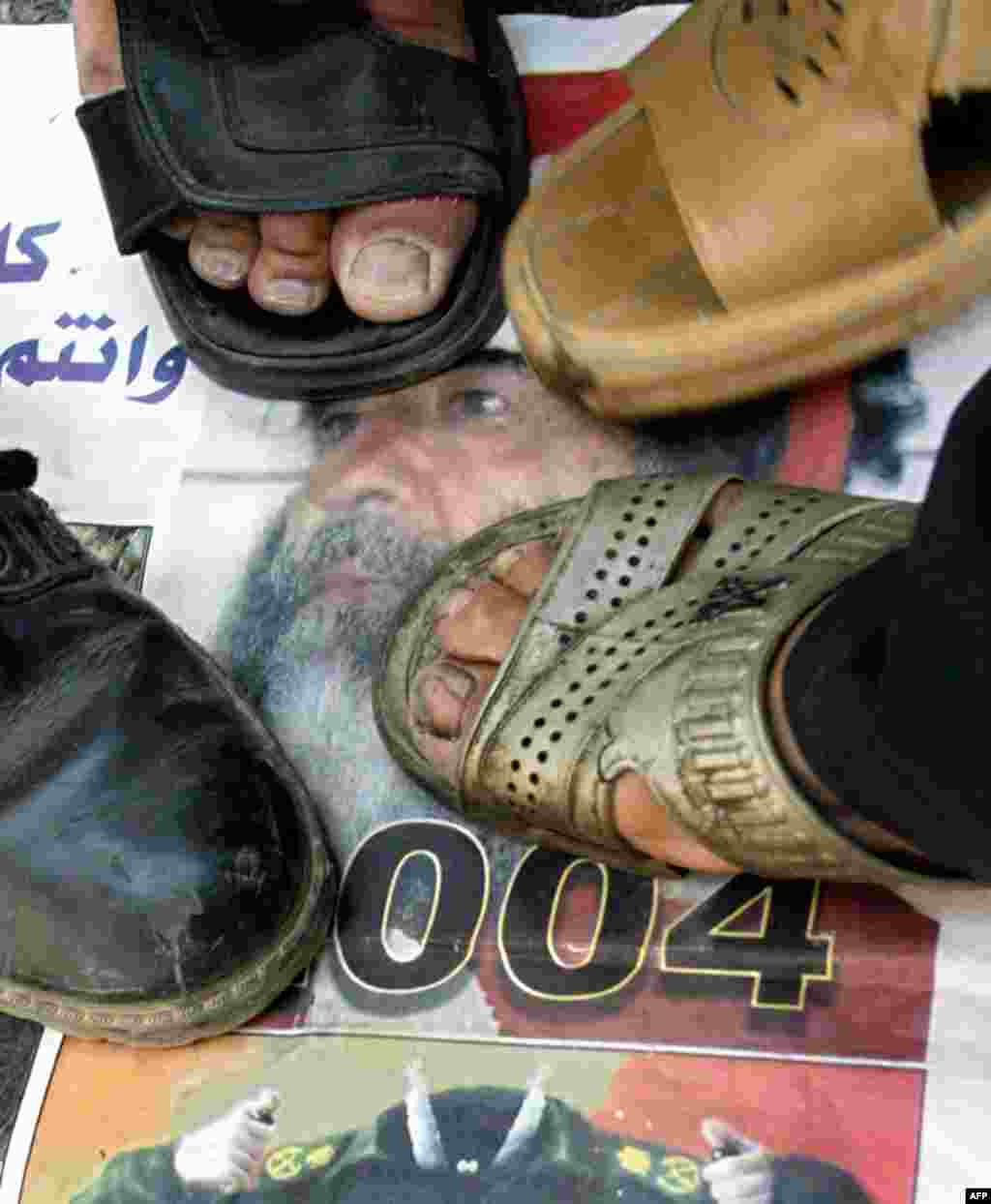 Iraqis stamp on Saddam Hussein's photo at a Baghdad demonstration in July 2004. He retained some support among Iraq's Sunni minority, but most Iraqis celebrated his downfall and welcomed his trial.