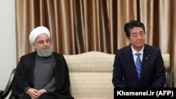 Japanese Prime Minister Shinzo Abe sits next to Iranian President Hassan Rohani (L) during a meeting with the supreme leader in Tehran, June 13, 2019