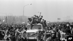 IRAN -- Ayatollah Khomeini Return from Exile 1979 -- Excited followers of the Ayatollah Khomeini, behind windshield, left, throng his motorcade as he leaves the airport for Behesht Zahra Cemetery, in Tehran, Iran, Feb. 1, 1979.