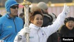 Ольга Шишигина бежит с пламенем зимних Азиатских игр во время эстафеты олимпийского огня в Алматы. 12 января 2011 года