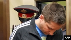 Police Major Denis Yevsyukov being escorted into a Moscow court on April 29
