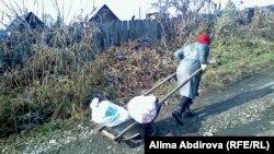 Құдықтан су тасып бара жатқан әйел. Шығыс Қазақстан облысы. Көрнекі сурет