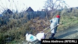 Woman hauls wheelbarrow in Zyryanovsk city eastern Kazakhstan