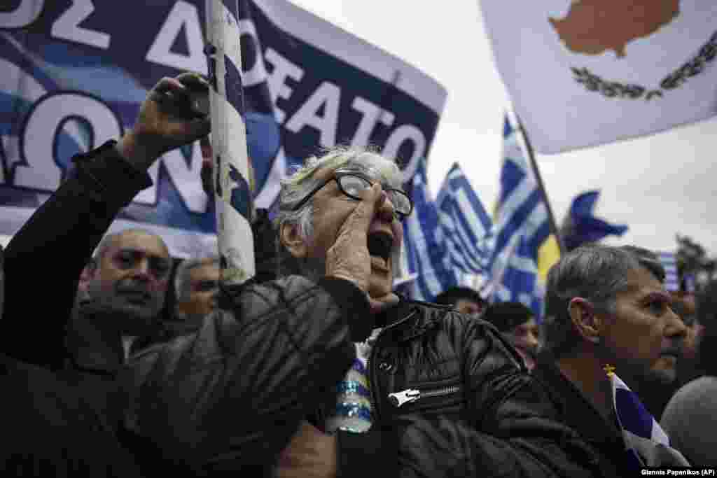 "Greeks chant slogans during the protest that police say attracted 90,000 people. Reuters estimated the crowd at ""hundreds of thousands."""