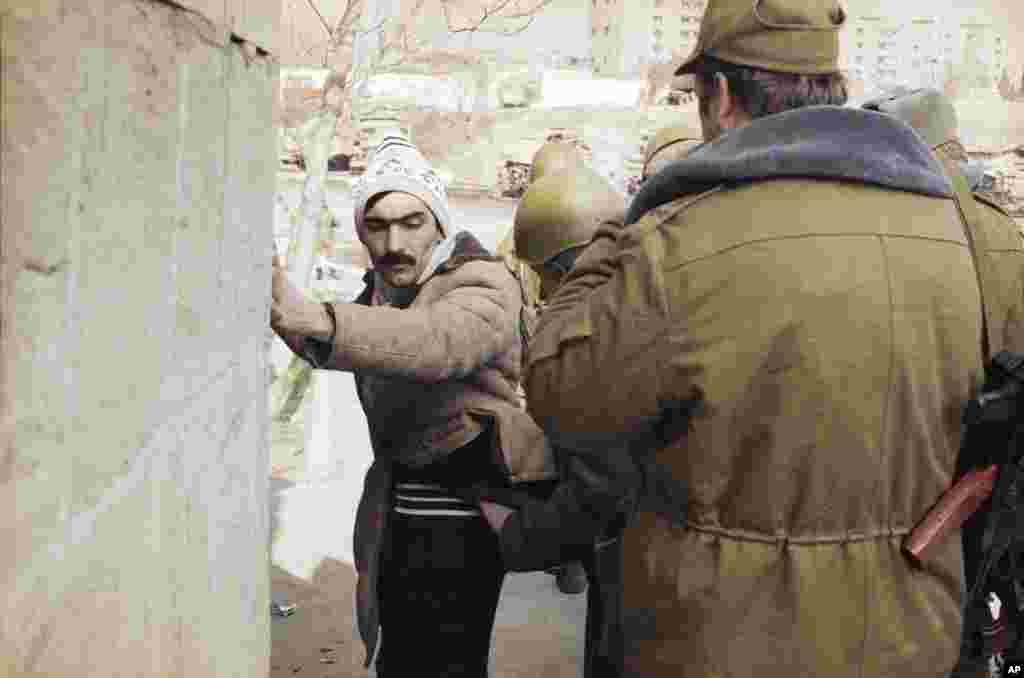 Soviet troops question a resident of the Azerbaijani capital on January 27 during a patrol to quell nationalist support. Thousands of Popular Front members and sympathizers were arrested and imprisoned.