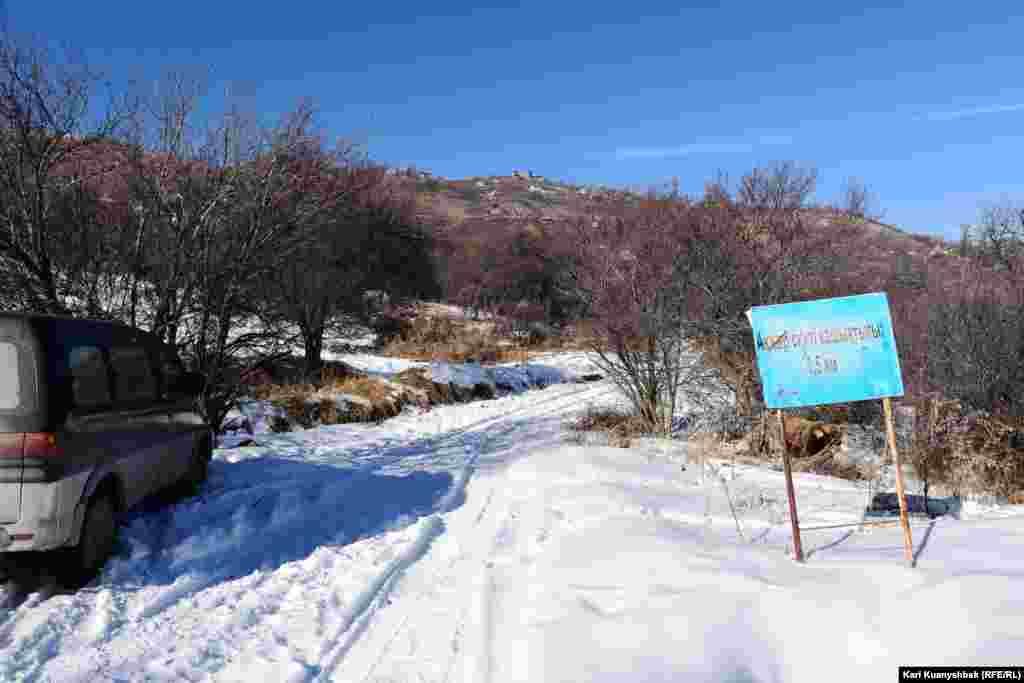 Знак, указывающий дорогу в скит в Аксайском ущелье. Путешественники, добирающиеся сюда на автомобиле, оставляют машины на этом месте и дальше поднимаются в гору пешком.