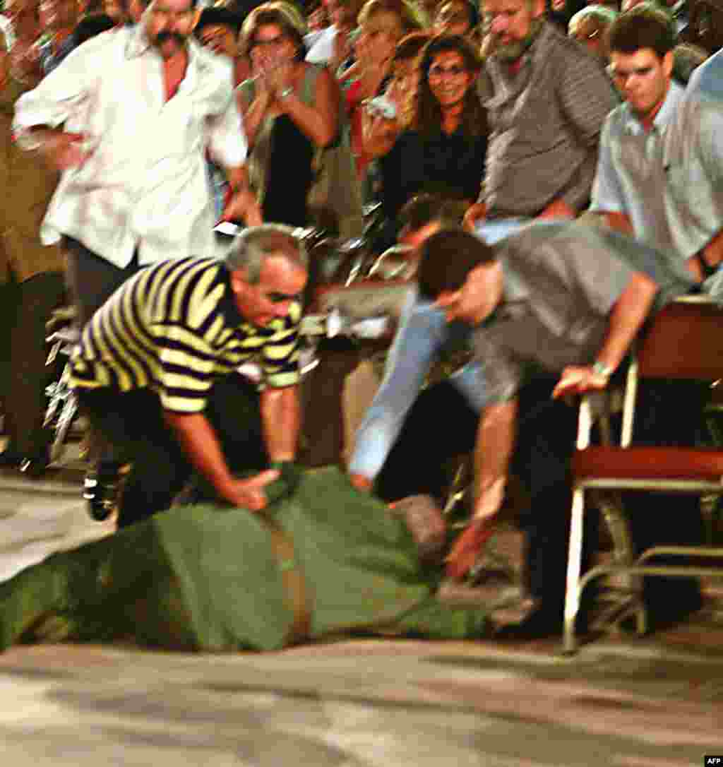 Castro (center) is helped by his bodyguards after he fell over at the end of a speech following a graduation ceremony in central Cuba in October 2004.