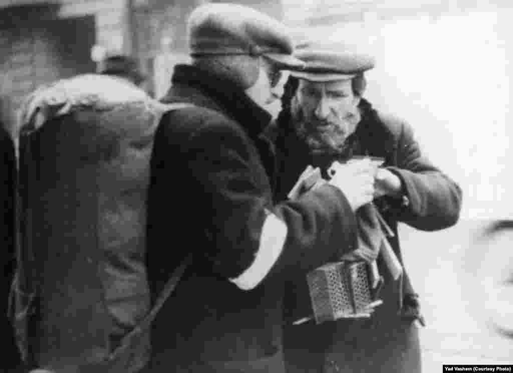 A Jew sells mouse traps in the ghetto.