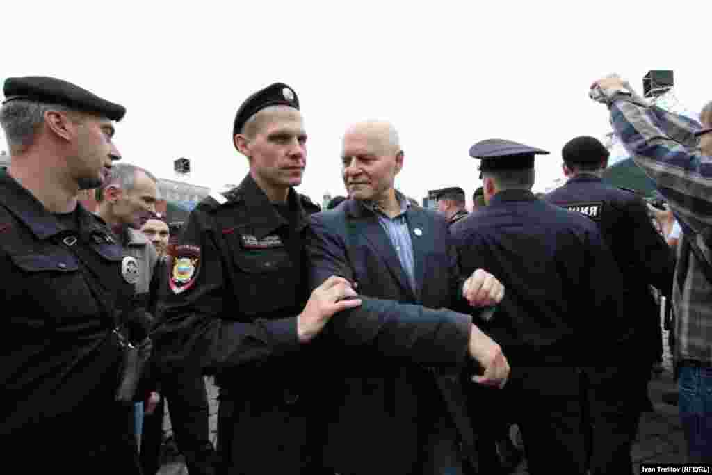 Mikhail Shneider of the Solidarity movement is led away by police.