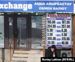 Молодой человек говорит по телефону возле пункта обмена валют. Алматы, 11 февраля 2014 года.