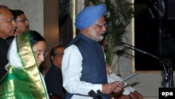 Manmohan Singh takes the oath as India's new prime minister as Indian President Pratibha Patil (left) stands by during the swearing-in ceremony in New Delhi on May 22.