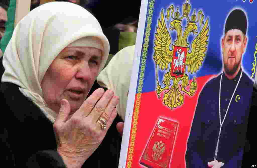 Чеченська жінка тримає фото Кадирова