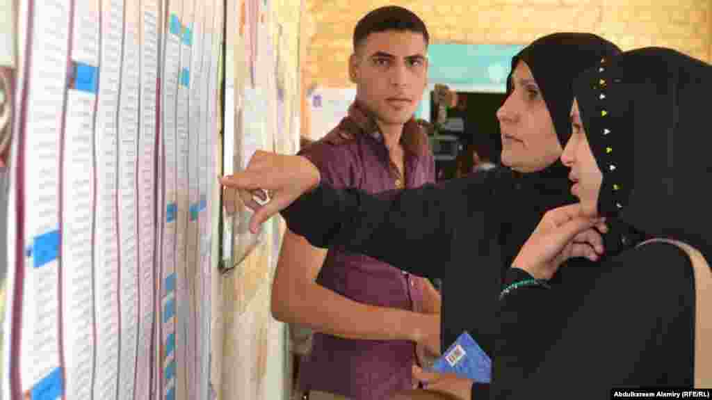 Women voters look for their names on voters' lists in Basra.