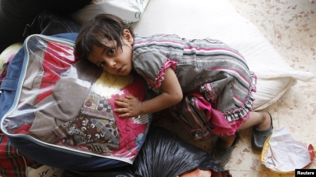 A Syrian girl lies on top of luggage at a makeshift refugee camp inside Iraq after crossing the Iraqi-Syrian border at Abu Kamal-Qaim, the main border post between the two countries, on July 24.