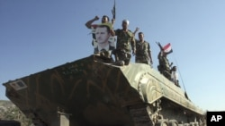 Syrian soldiers shout pro-President Bashar al-Assad slogans as they stand on their tank on a flatbed truck heading out of the city of Edleb on August 10.