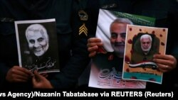 Iranian Guards hold a picture of the late Iranian Major-General Qassem Soleimani and an Iraqi militia leader, during a protest against their targeted killing. January 3, 2019