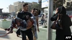 Një person e ndihmon të plagosurin nga sulmi i sotëm në Kabul