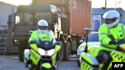 Police escort a British army truck carrying a freight container laden with Skripal's car as part of the UK investigation into the nerve agent attack on Skripal in Salisbury, March 16, 2018.